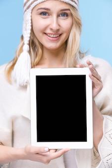 Vista frontal mulher sorridente com um tablet