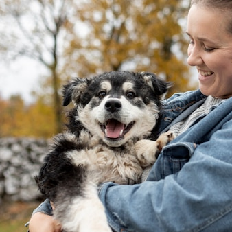 Vista frontal mulher sorridente segurando cachorro fofo