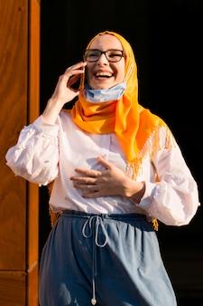 Vista frontal mulher sorridente segurando o telefone