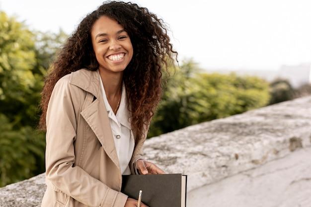Vista frontal mulher sorridente segurando um livro com espaço de cópia