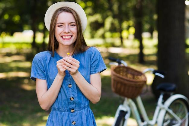 Vista frontal mulher sorridente segurando uma flor