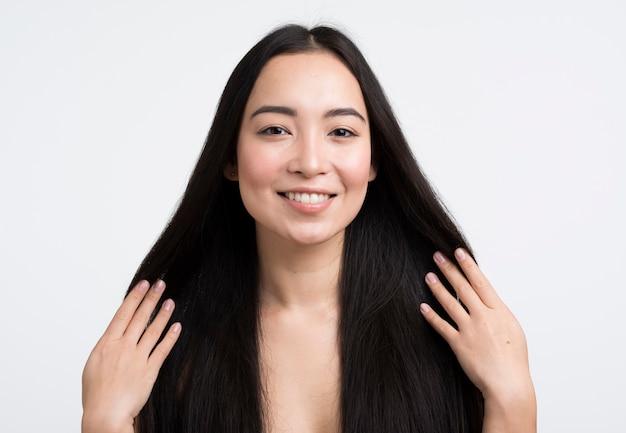 Vista frontal mulher tocando seu cabelo
