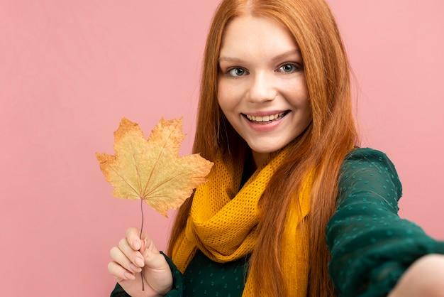 Vista frontal mulher tomando selfie com folha