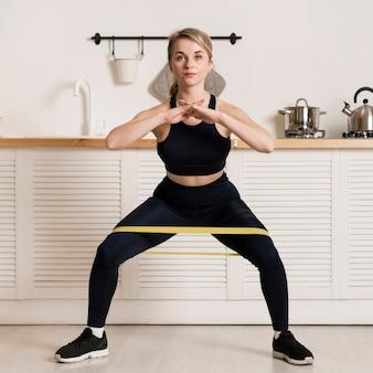 Vista frontal mulher treinando com elástico