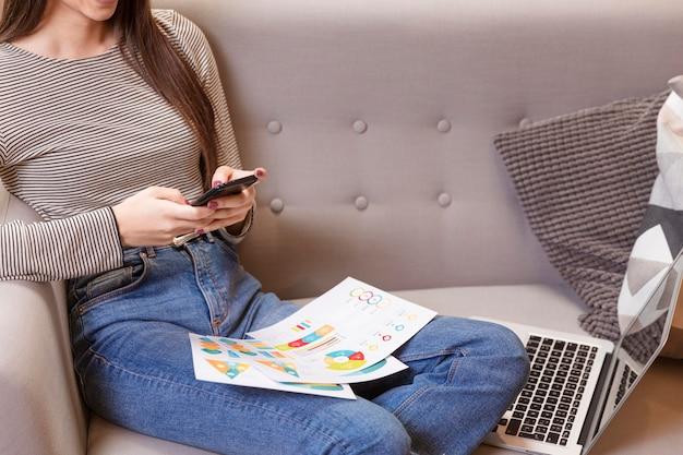 Vista frontal mulher usando gráficos e telefone celular