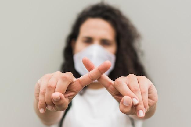 Vista frontal mulher vestindo máscara médica e formando um x com os dedos