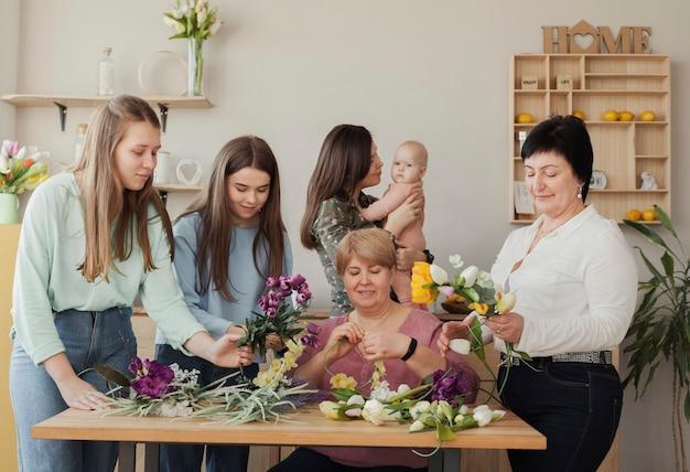 Vista frontal mulheres e bebê em pé ao redor de uma mesa