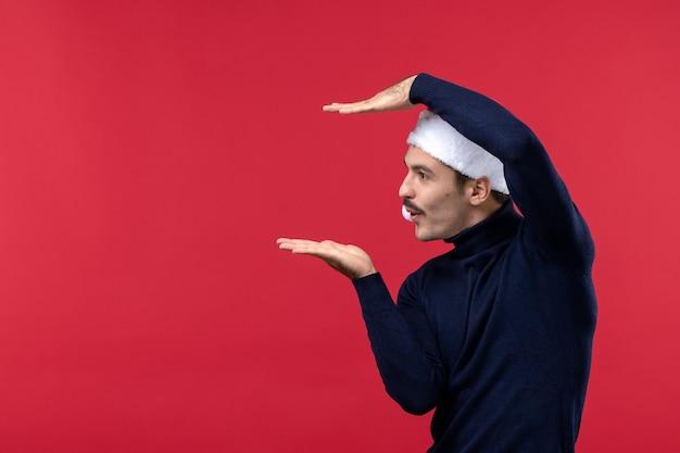 Vista frontal normal do sexo masculino mostrando o tamanho em fundo vermelho Foto gratuita