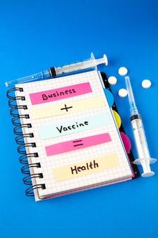 Vista frontal, nota de saúde de vacina de negócios com vacina e injeção em fundo azul