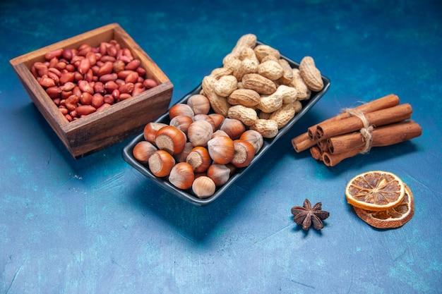 Vista frontal, nozes frescas, canela, amendoins e avelãs na cor azul, lanche cips, nozes, nozes, foto, planta, árvore