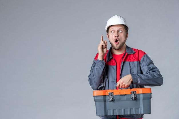 Vista frontal, o construtor masculino com estojo de ferramentas de fixação uniforme tem uma ideia no fundo cinza