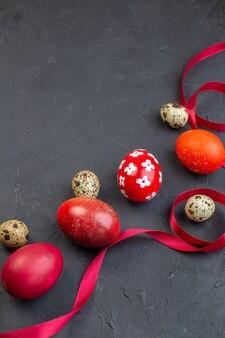 Vista frontal ovos de páscoa coloridos com ovos de codorna e laço vermelho na superfície escura ornamentado primavera colorido conceito colorido feriado pássaro