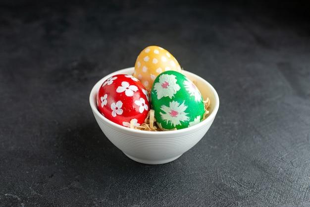 Vista frontal ovos de páscoa coloridos dentro da placa no fundo escuro conceito horizontal ornamentado primavera colorido