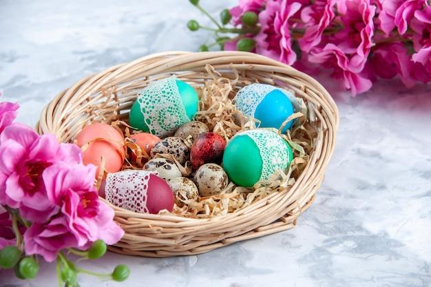 Vista frontal ovos de páscoa coloridos dentro da superfície branca da cesta