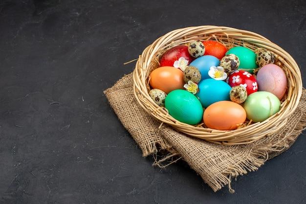 Vista frontal ovos de páscoa coloridos dentro de uma cesta em uma superfície escura