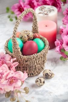 Vista frontal ovos de páscoa coloridos dentro de uma cesta projetada com flores na superfície branca