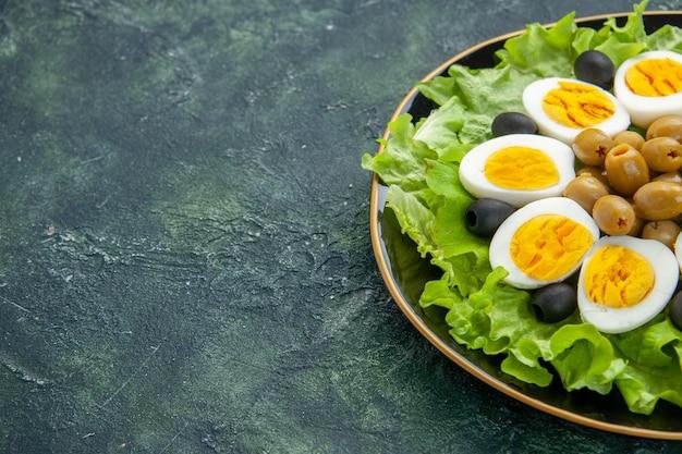 Vista frontal ovos fatiados cozidos com azeitonas e salada verde em fundo azul escuro