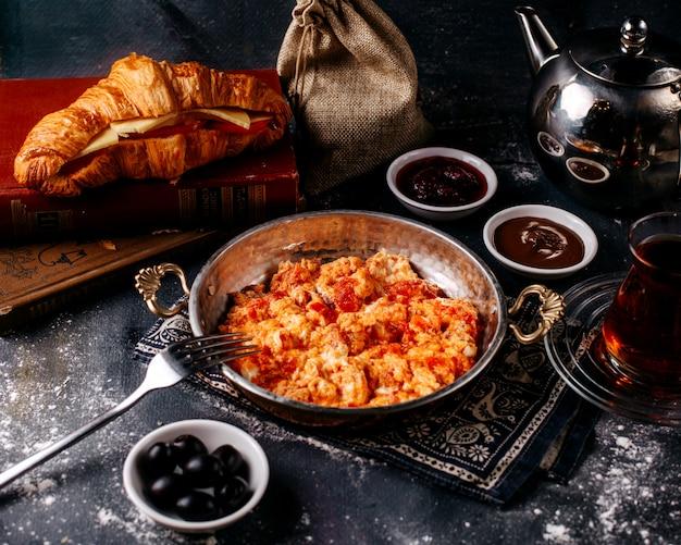 Vista frontal ovos tomates vermelhos fritos junto com pão fresco azeitonas e chá na superfície brilhante