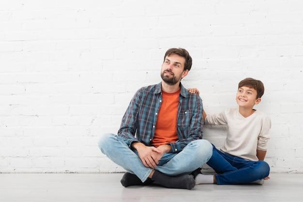 Vista frontal pai e filho, olhando para longe