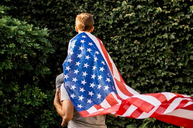 Vista frontal pai e filho usando bandeira eua