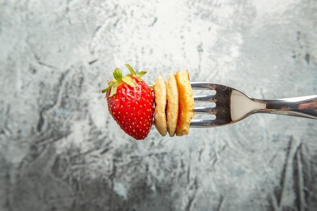 Vista frontal, panquecas com morango no garfo e bolo de superfície leve, sobremesa de frutas