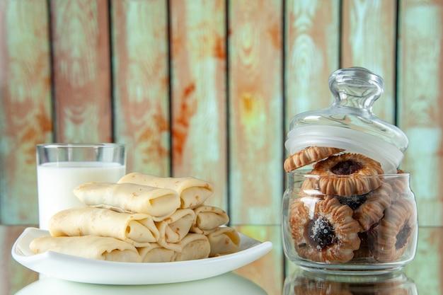 Vista frontal panquecas doces enroladas com leite e biscoitos em fundo claro farinha de flores bolo cor de café da manhã torta de manhã comida