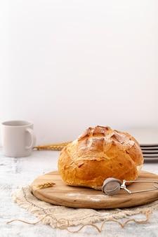 Vista frontal pão cozido com trigo na placa de madeira