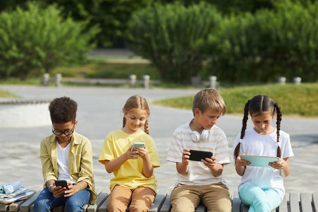 Vista frontal para um grupo multiétnico de crianças usando tablets e smartphones enquanto estão sentadas em uma fileira ao ar livre sob a luz do sol