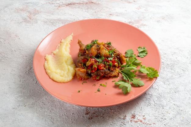 Vista frontal, pedacinhos de carne com purê de batatas e verduras na superfície branca