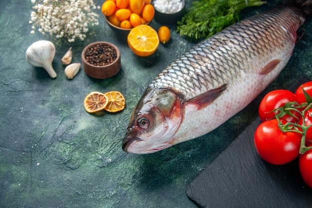 Vista frontal peixe cru fresco com tomates e verdes na superfície escura alimentos saúde água peixes cor refeição dieta salada pimenta frutos do mar oceano