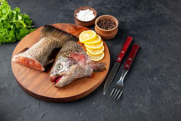 Vista frontal peixe fresco fatiado com rodelas de limão em fundo escuro refeição de frutos do mar oceano carne do mar comida refeição salada peixes aquáticos
