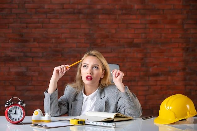 Vista frontal pensando engenheira sentada no escritório