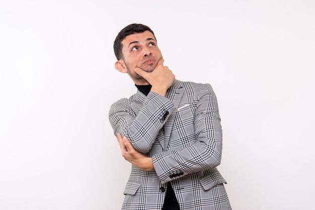 Vista frontal pensando homem bonito de terno em pé sobre fundo branco