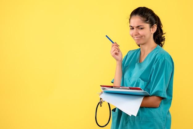 Vista frontal pensando jovem médica verificando papéis em pé sobre fundo amarelo