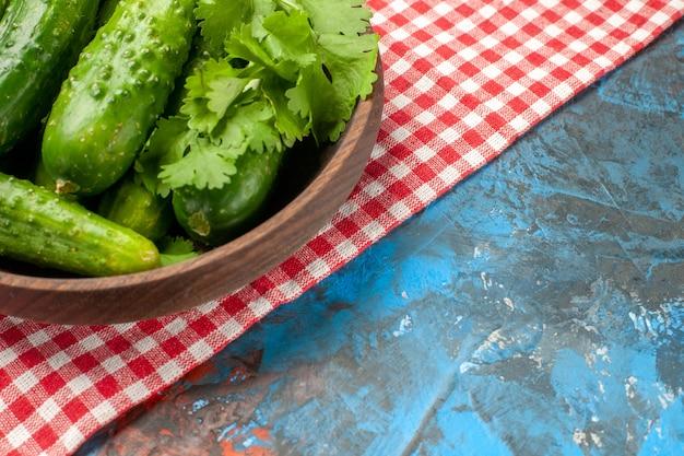 Vista frontal pepinos frescos dentro do prato no fundo azul saúde cor madura salada alimentar dieta