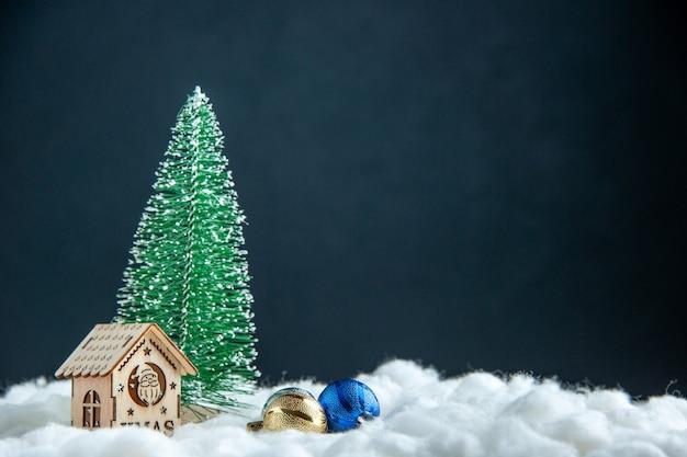 Vista frontal pequena árvore de natal pequena casa de madeira bolas de árvore de natal em superfície escura