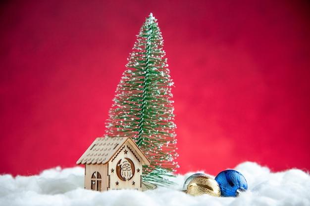 Vista frontal pequena casa de madeira com árvore de natal na superfície vermelha