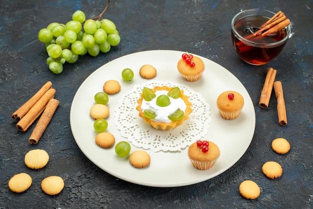 Vista frontal pequeno bolo com creme e uvas verdes dentro do prato junto com biscoitos de canela e chá na superfície escura doce de frutas
