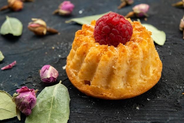 Vista frontal pequeno bolo com framboesa no topo isolado com pequenas flores na superfície escura açúcar doce