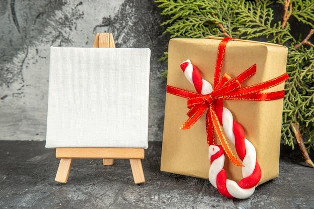 Vista frontal pequeno presente amarrado com fita vermelha natal candy mini canvas cavalete de madeira ramo de pinho cinza