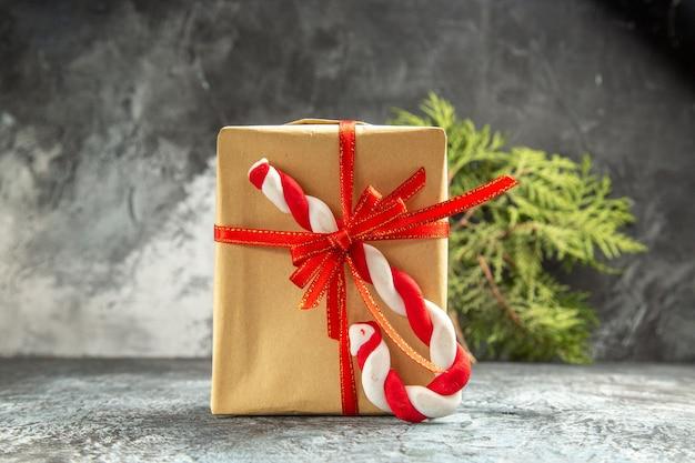 Vista frontal pequeno presente amarrado com fita vermelha ramo de pinho doce de natal em cinza