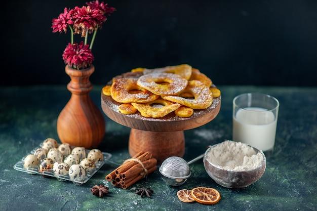 Vista frontal, pequenos bolos deliciosos em forma de anel de abacaxi com leite na superfície escura