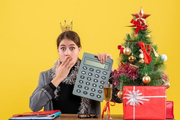 Vista frontal perplexa garota com coroa sentada à mesa segurando calculadora árvore de natal e presentes