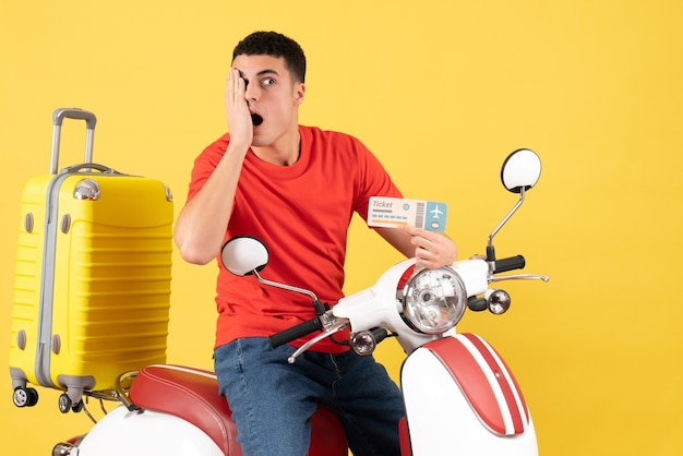 Vista frontal perplexo jovem do sexo masculino em roupas casuais em ciclomotor segurando o bilhete de viagem