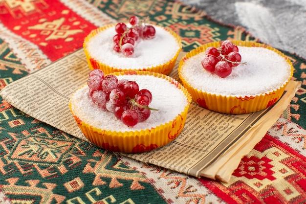 Vista frontal perto deliciosos bolos de cranberry com cranberries vermelhas por cima com açúcar em pó