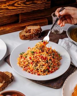 Vista frontal picada de arroz com legumes coloridos na superfície marrom