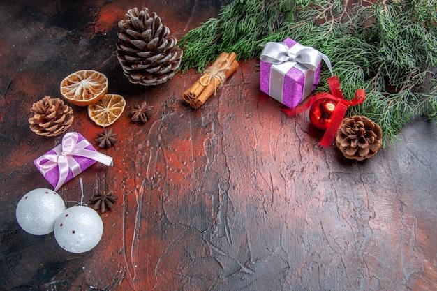 Vista frontal pinheiro galhos cones natal tree brinquedos canela seca rodelas de limão anis estrelado em fundo vermelho escuro espaço livre foto de ano novo