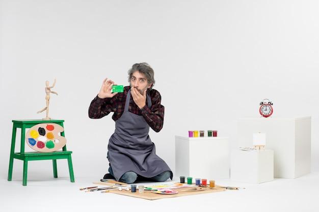Vista frontal pintor masculino segurando cartão do banco na luz de fundo arte pintura cor artista dinheiro trabalho pintura