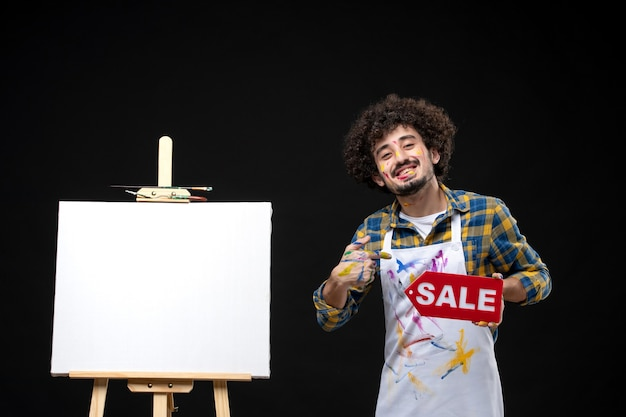 Vista frontal, pintor masculino segurando venda escrita na parede escura pinturas de quadros cavalete preto compras arte desenho