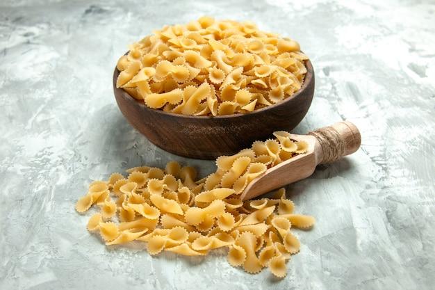 Vista frontal, pouca massa crua dentro do prato, foto clara, muitas massas de farinha